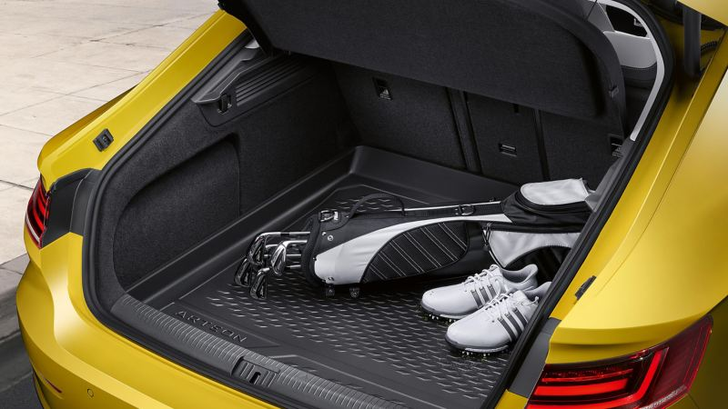 The boot of a yellow Volkswagen Arteon, open with golf clubs inside.