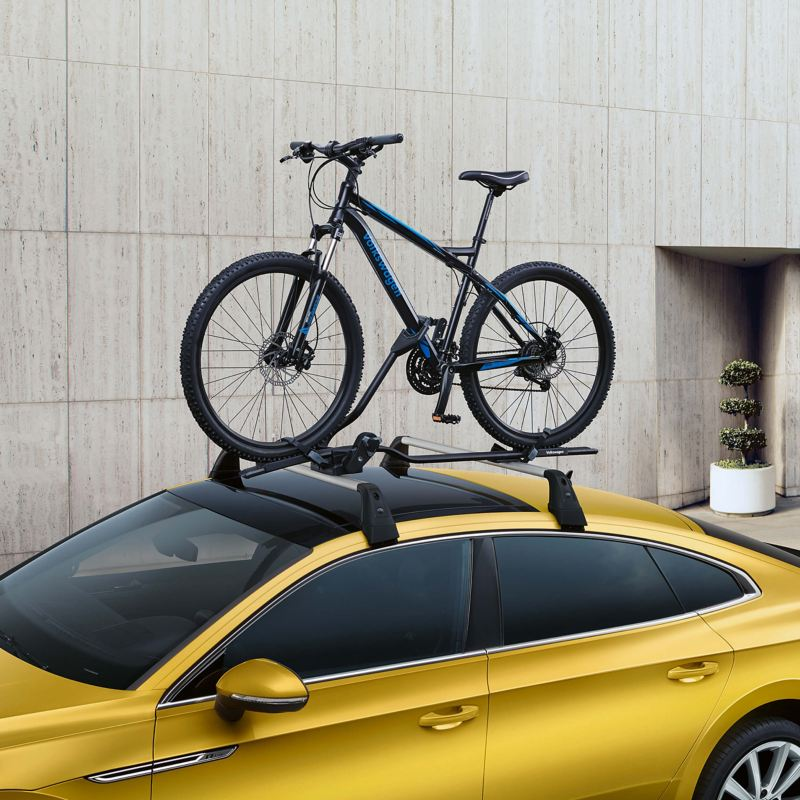 A yellow Volkswagen Arteon with a bike and cycle rack on the roof.