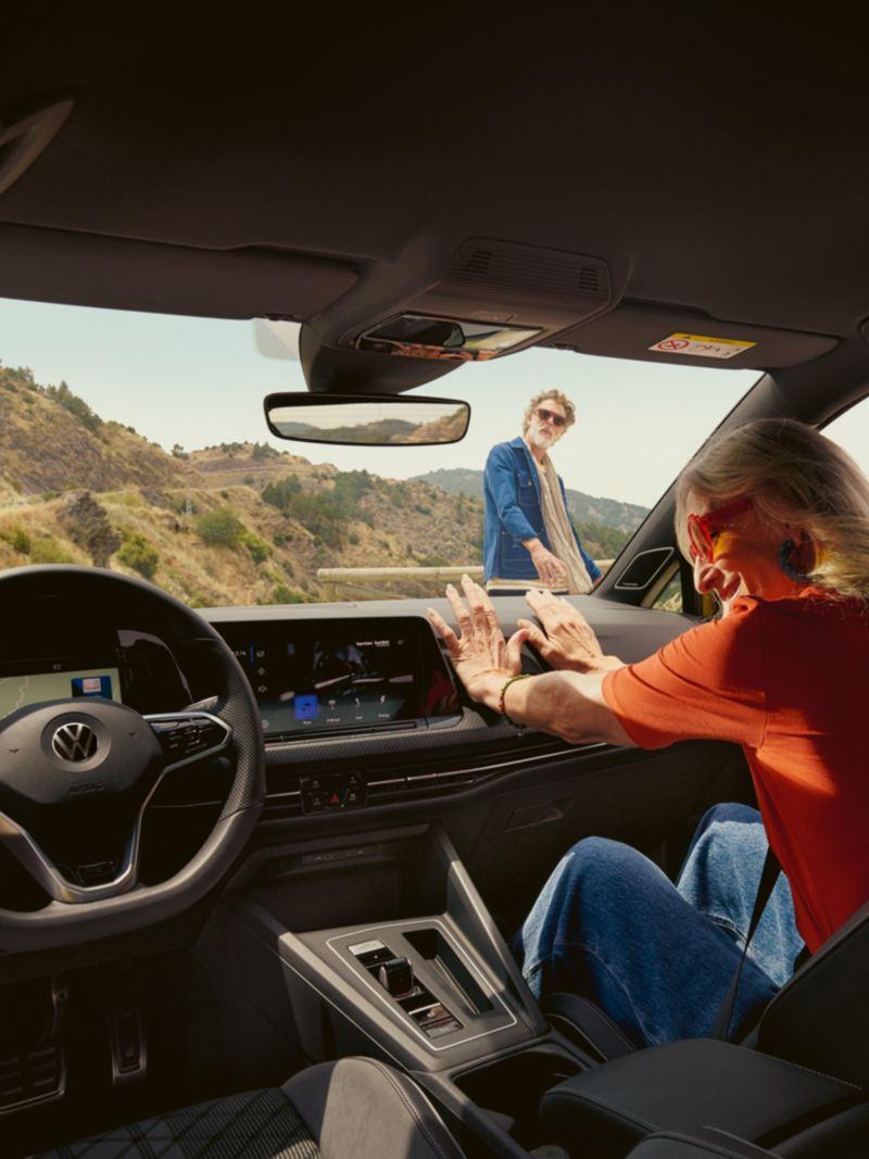 Une femme se détend sur le siège passager avant d'une VW Golf.