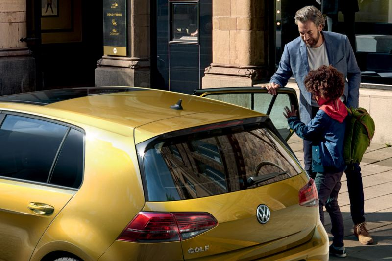 VW Golf parking on the street, family getting in