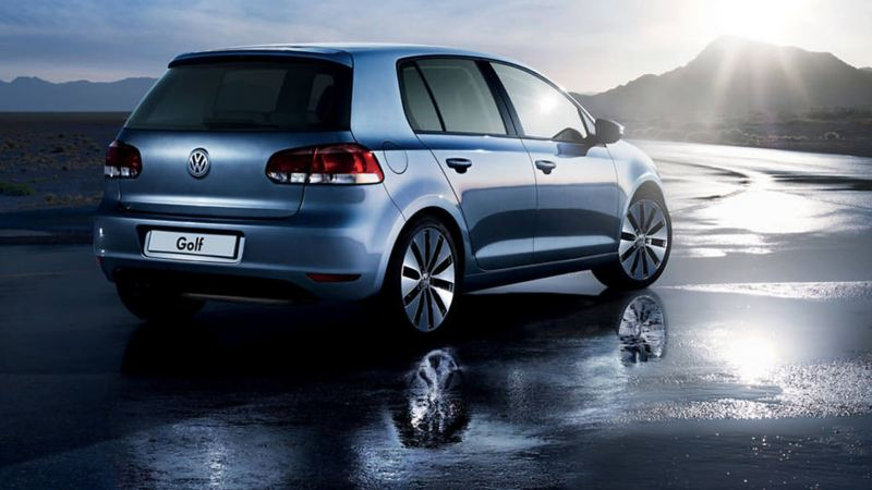 Rear shot of a blue Volkswagen Golf S, on a wet beach.