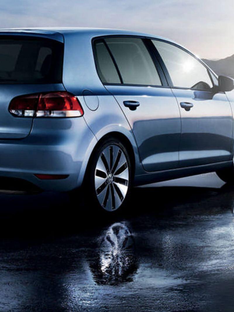 Rear shot of a blue Volkswagen Golf S, on a wet beach.