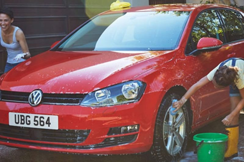 A red Volkswagen Golf, being washed by two friends.