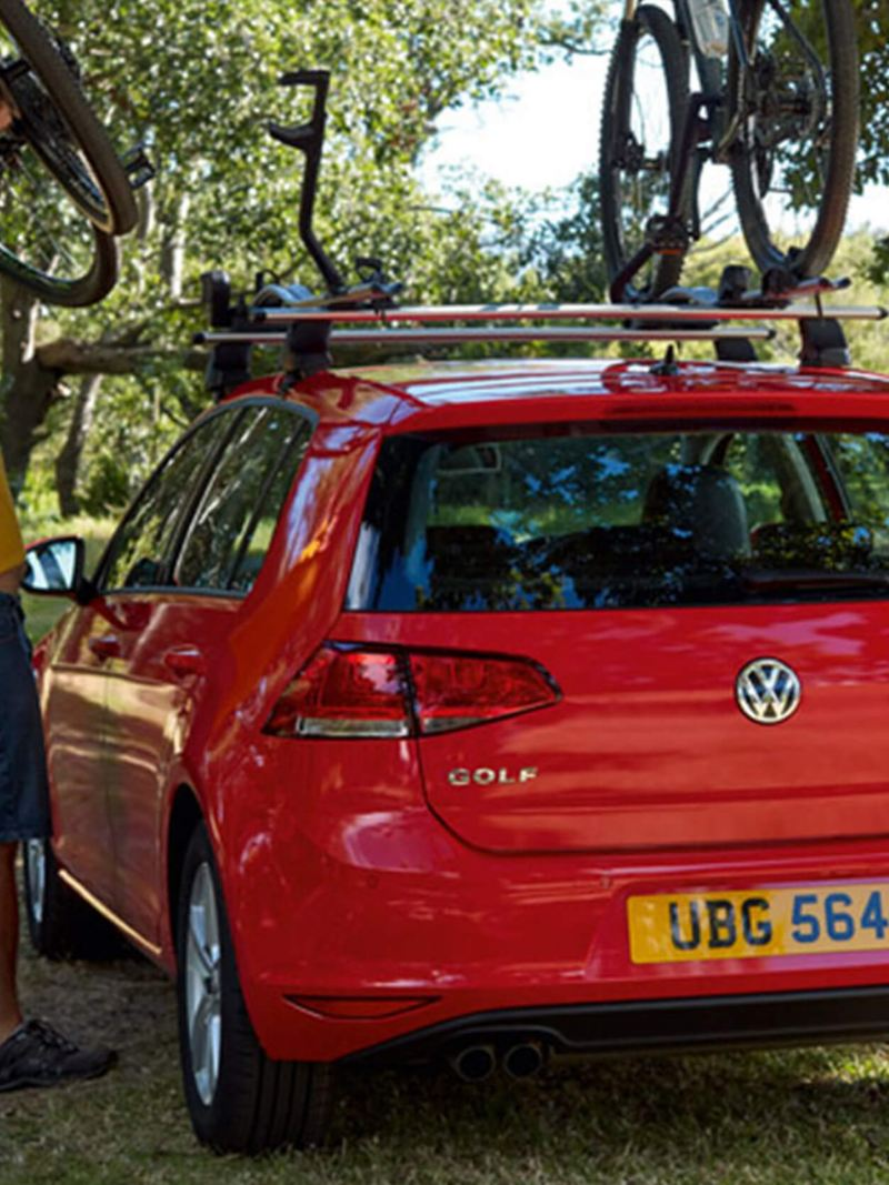 A man hitching his bike to the roof rake of a Volkswagen Golf, surrounded by woodland