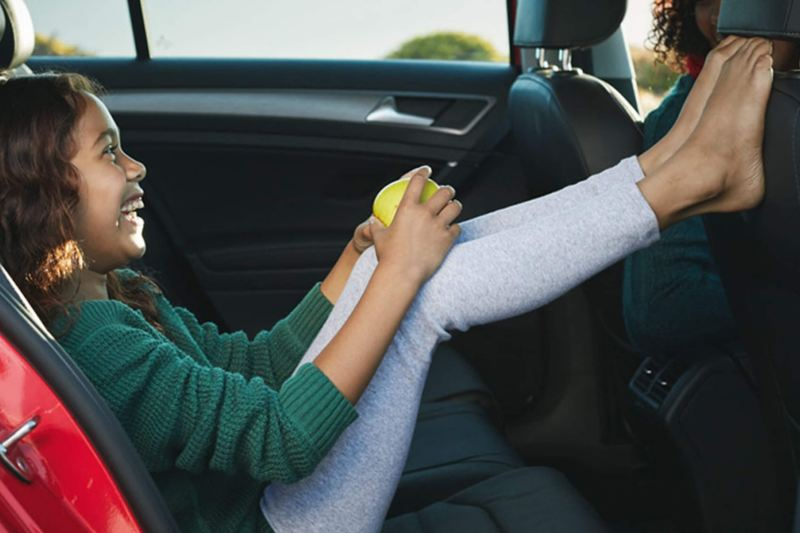 A young girl in the back passenger seat of a Volkswagen golf, with her feet up on the front seat.