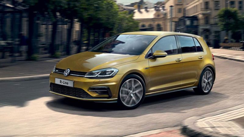A gold Volkswagen Golf R-Line, driving through an old city.
