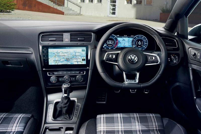 Interior shot of a Volkswagen Golf, steering wheel and dashboard.