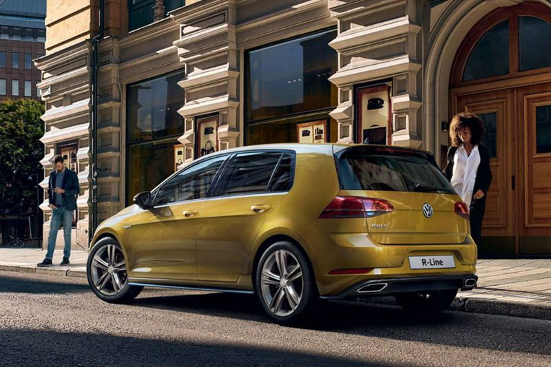 A gold Volkswagen Golf R-Line, parked outside an old city building, with a lady approaching.