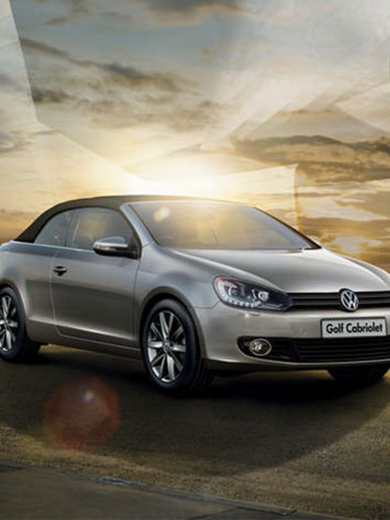 3/4 front view of a silver Volkswagen Golf Cabriolet, sun setting in the background.