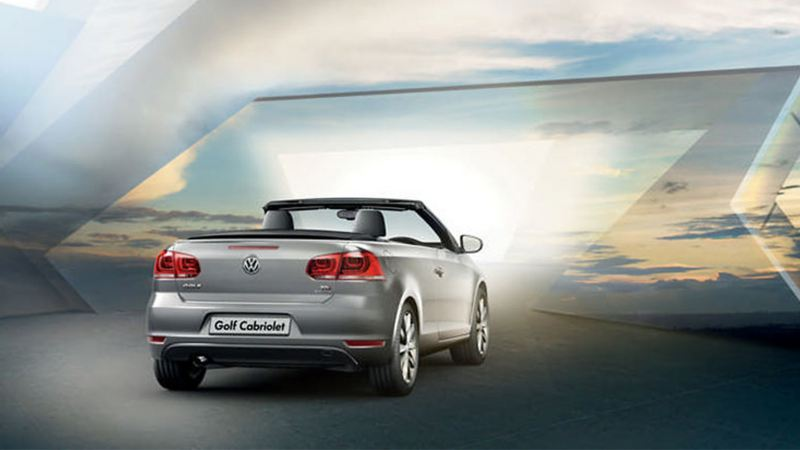 Rear view of a silver Volkswagen Golf Cabriolet, with the roof down.