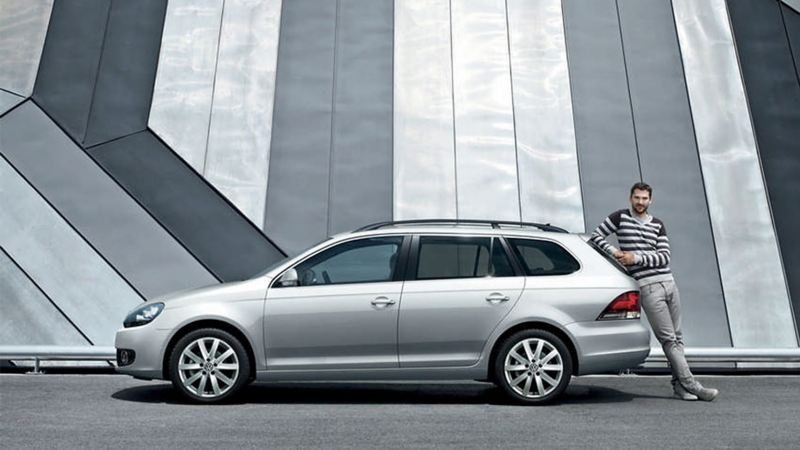 A man leaning on the back of a silver Volkswagen Golf Estate.