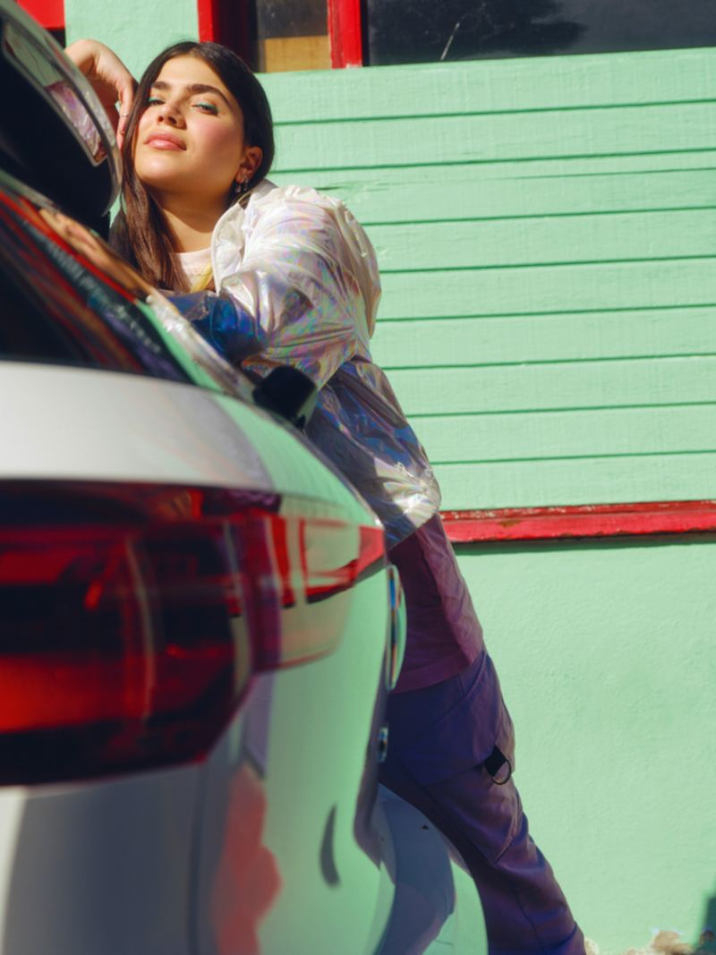 VW Golf GTE in white, rear view, woman leans against vehicle