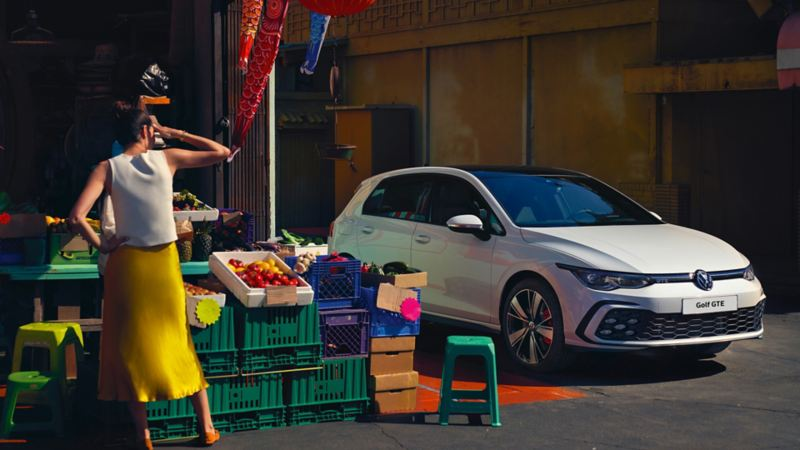 A woman looking at Golf GTE outside a fruit and veg market stall