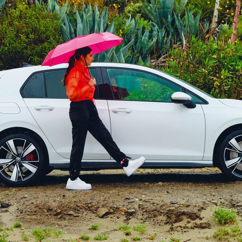 Car on the beach and a lady with an umbrella