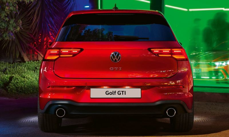 VW Golf GTI in red, rear view, parked in front of a club