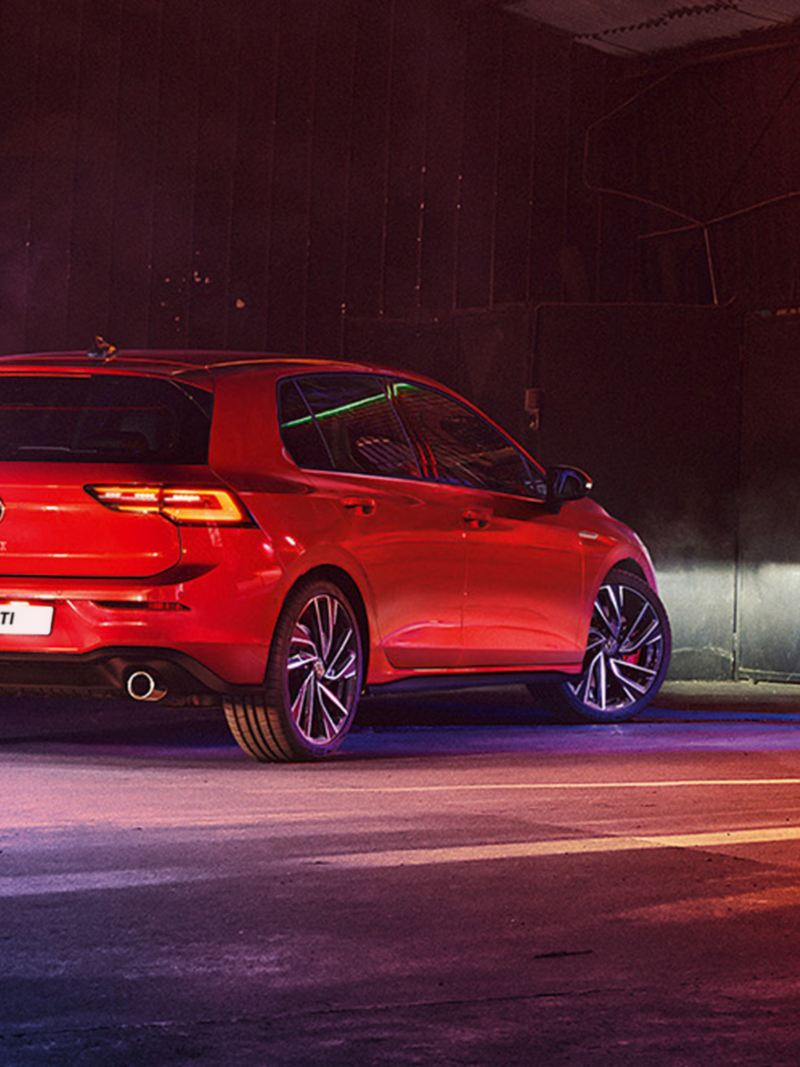 VW Golf GTI in red, rear view, parked in a warehouse