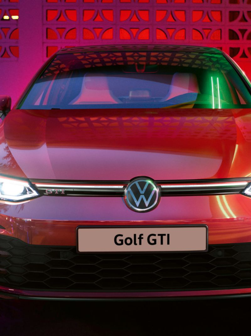 VW Golf GTI in red, front view, glowing IQ.Light headlights