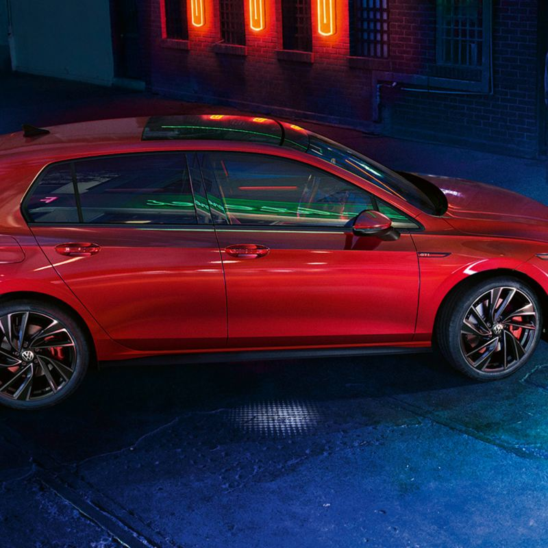 VW Golf GTI in red, side view, parked on a street