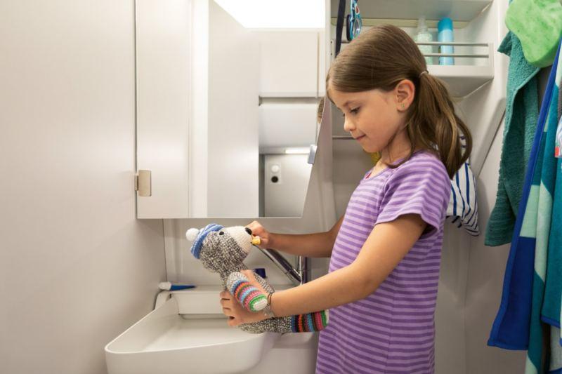 Ein kleines Mädchen steht im Bad des Grand California. Sie putzt ihrem Teddy die Zähne.