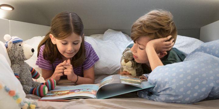 Ein kleiner Junge und seine Schwester liegen im Hochbett des Grand California und lesen gemeinsam ein Buch.