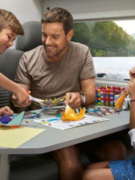 Ein Vater und seine Kinder sitzen im Wohnbereich des Grand California am Tisch und spielen. Im Hintergrund ist die Mutter zu sehen. Sie liegt im Bett und liest ein Buch.