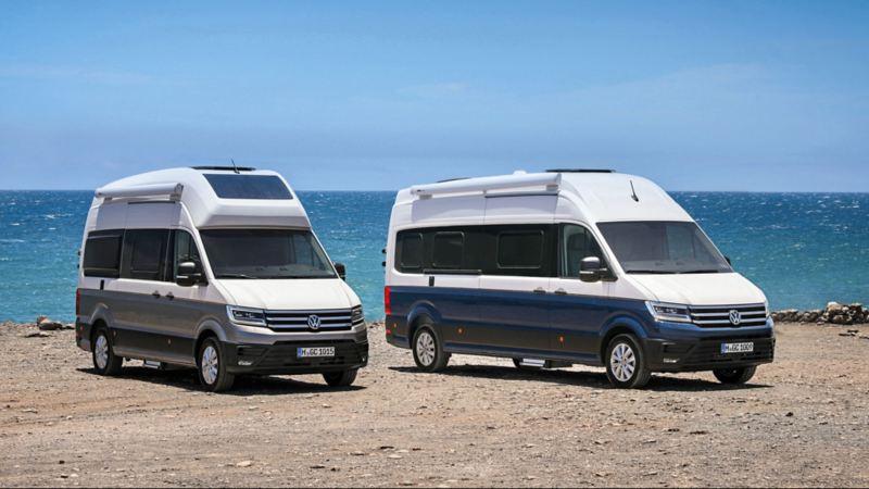 Vista 3/4 frontale di due Grand California Volkswagen parcheggiati in riva al mare.