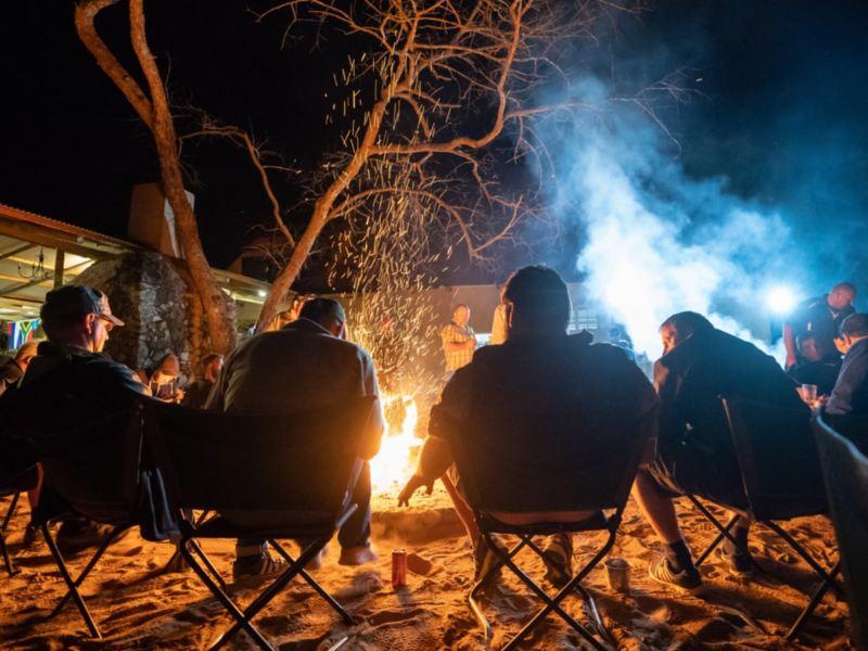 Einige Teilnehmer des Spirit of Amarok 2018 sitzen abends gemeinsam am Lagerfeuer.