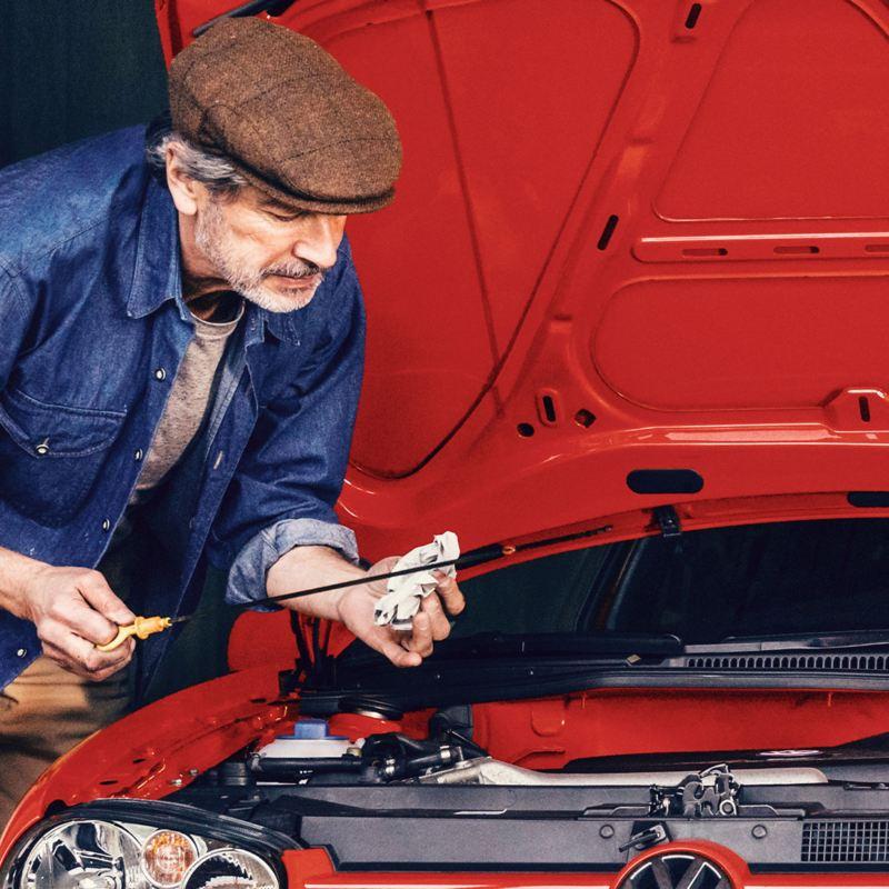 Hombre haciendo uso de la guía de refacciones Volkswagen para arreglar su automóvil
