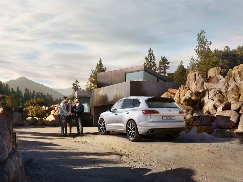 White Volkswagen Touareg, next to a mountain retreat.