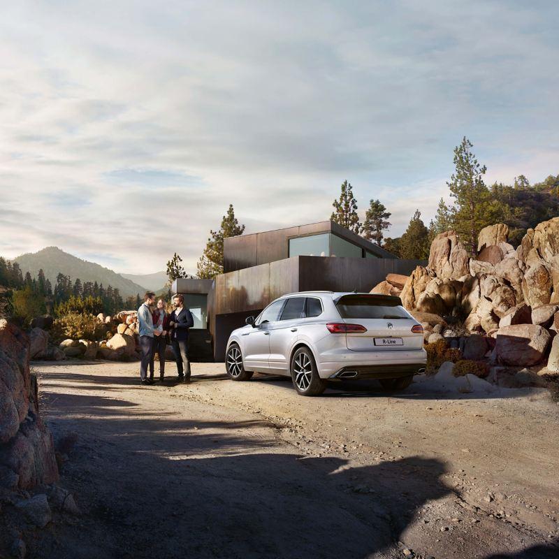 White Volkswagen Touareg, next to a mountain retreat.