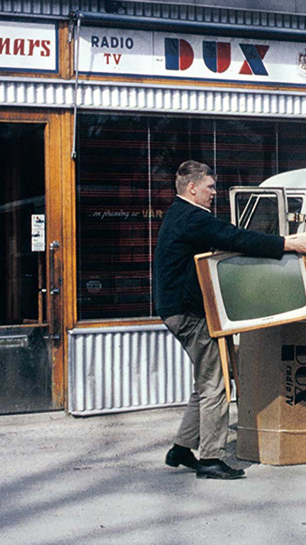 Två män lastar ut tv-apparater ur rödvit Volkswagen Transporter