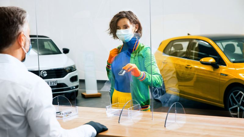 A woman wearing a face mask hands her car keys to a Volkswagen representative behind a protective screen