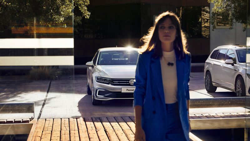 A lady in a suit walking away from a car park with the new Passat in the background