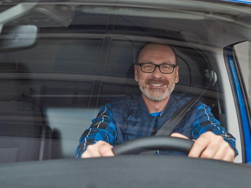 Ein lächelnder Mann am Lenkrad eines Volkswagen Nutzfahrzeuges.