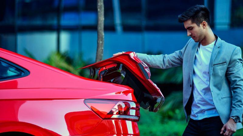 Hombre abriendo la cajueula de Virtus de Volkswagen