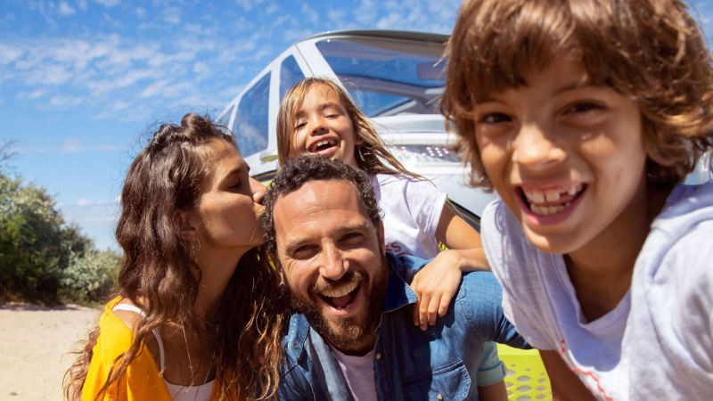 A family smiling in front of a Volkswagen vehicle