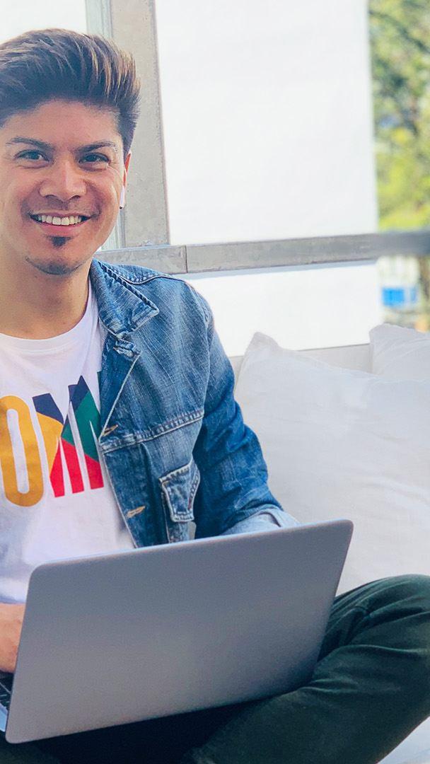 Mann mit Laptop schaut in die Kamera