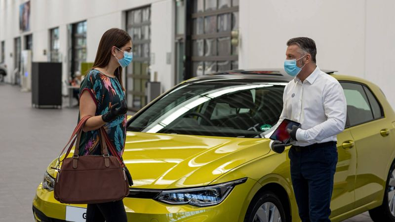 A woman wearing a face mask stands socially distanced from a Volkswagen representitive who is also wearing a mask