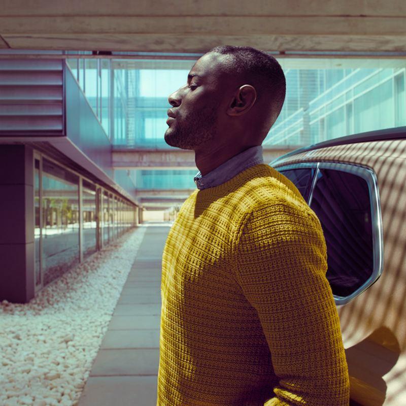 Man standing in front of a Volkswagen car