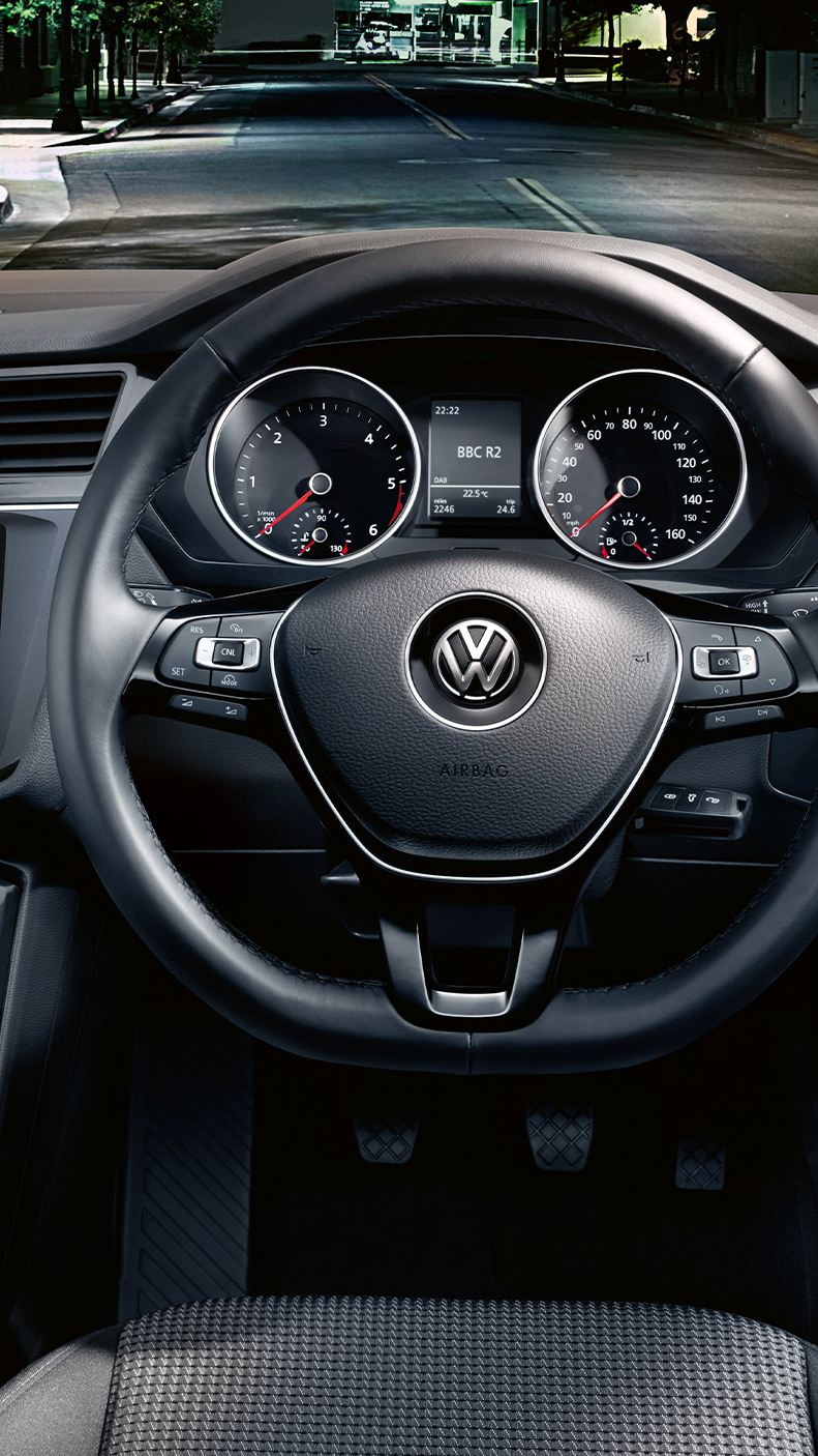 Interior shot of a Volkswagen, steering wheel and dashboard.