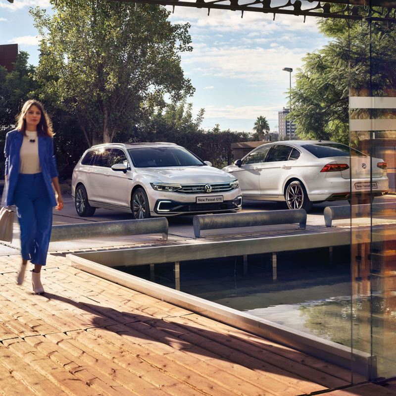A woman walking near two Passat GTE cars