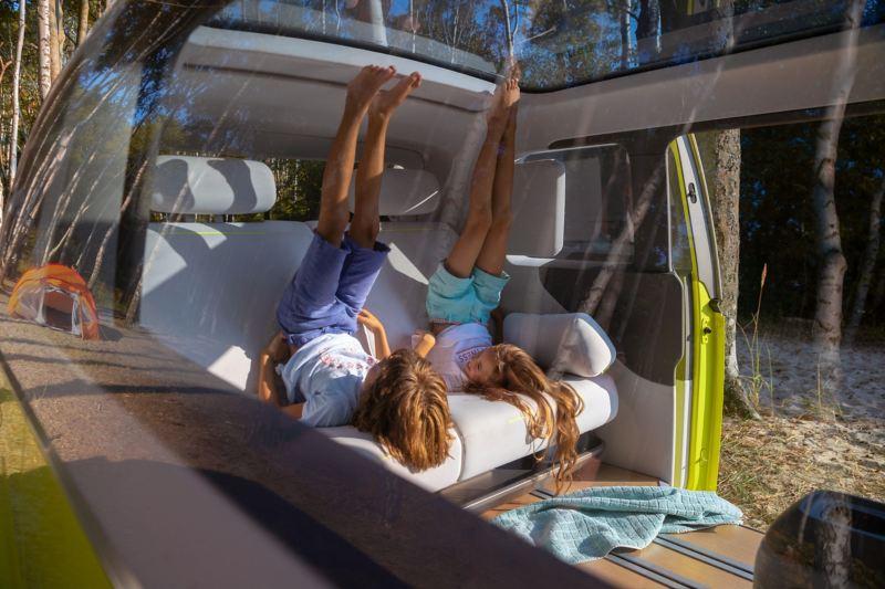 Um rapaz e uma rapariga fazem exercício no interior do Volkswagen ID. Buzz.