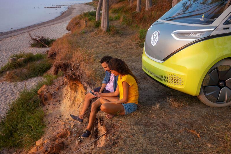 Eine Frau und ein Mann sitzen vor dem Volkswagen ID.Buzz an einem Strand.