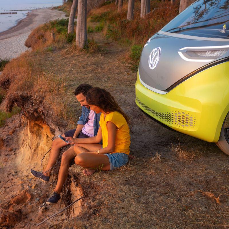 Volkswagen ID.Buzz kuvattuna rantatörmällä, auton keula näkyy kuvassa ja auton edessä on mies ja nainen selaamassa älypuhelinta ilta-auringon valaisemana