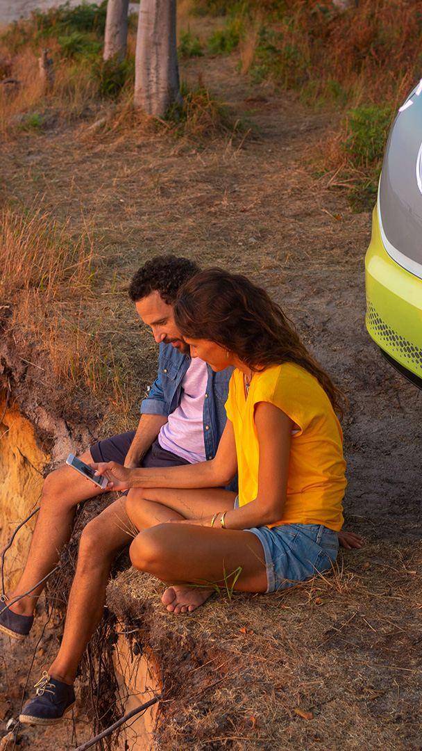 Un couple assis regarde un smartphone, leur Volkswagen en arrière-plan