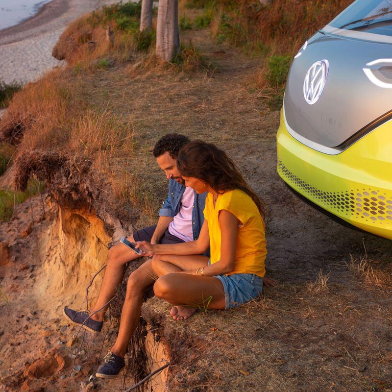 Nuori pariskunta katsoo kuvia kännykästä hiekkarannalla VW id Buzz auton edessä