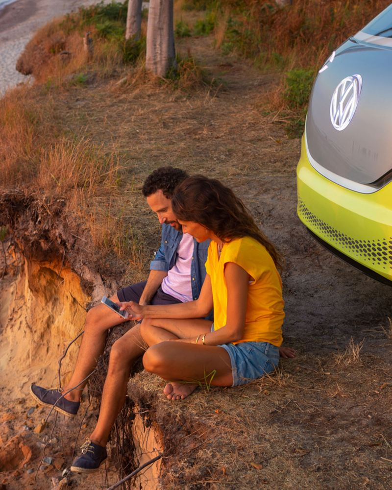 A couple is sitting on the edge of a cliff, the ID Buzz stands in the background