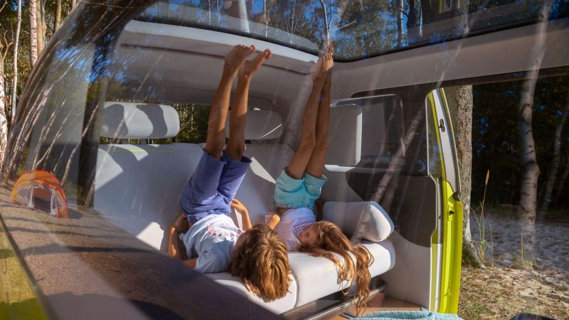 The interiour of the ID. Buzz with its spacious backseat and panoramic roof offers a lot of space for children
