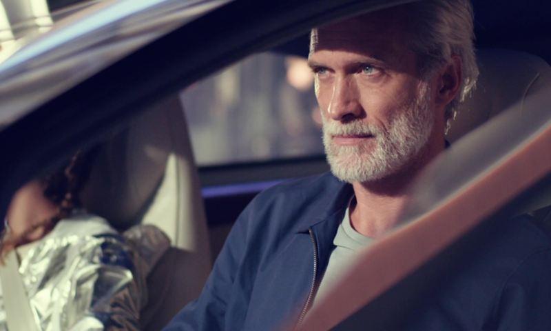 Un homme mature conduisant une voiture électrique