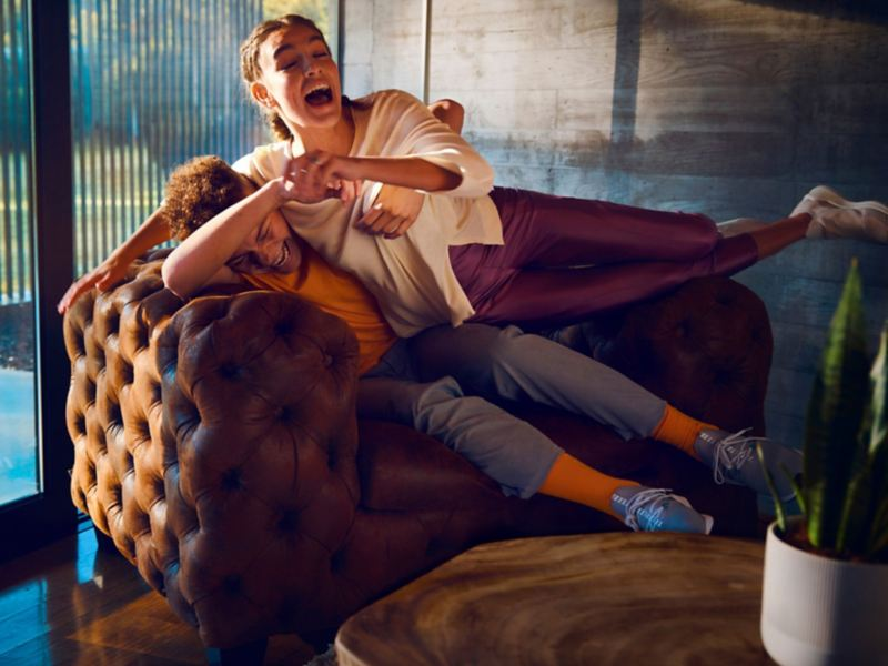 Teenagers playing on a sofa